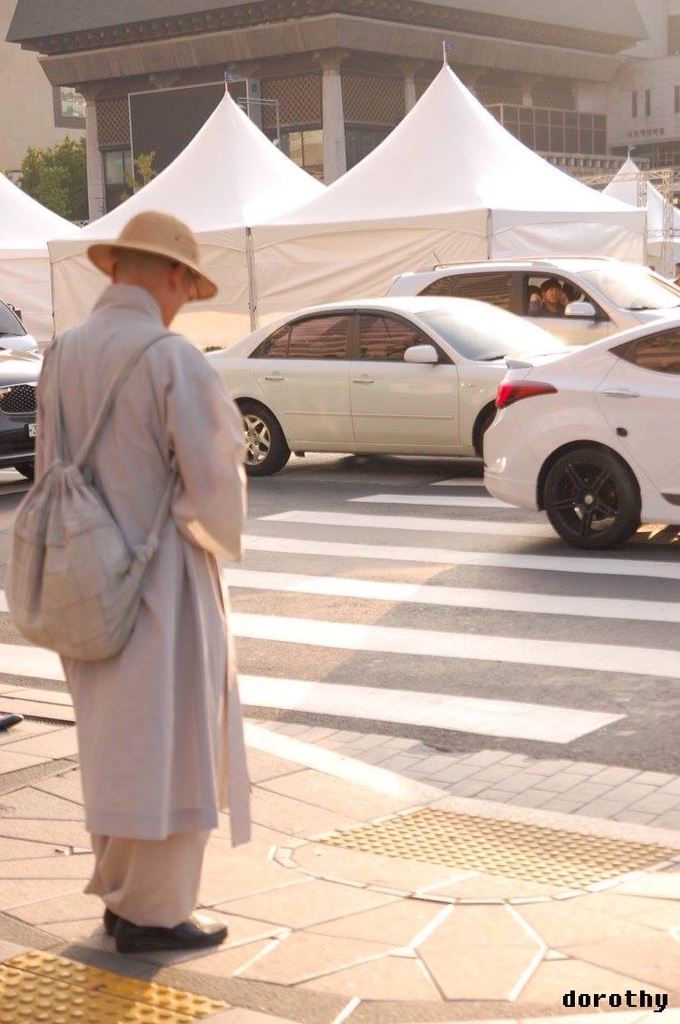 A person standing at a Zebra crossing. The other side of the road has tents put up. There are cars on the road.